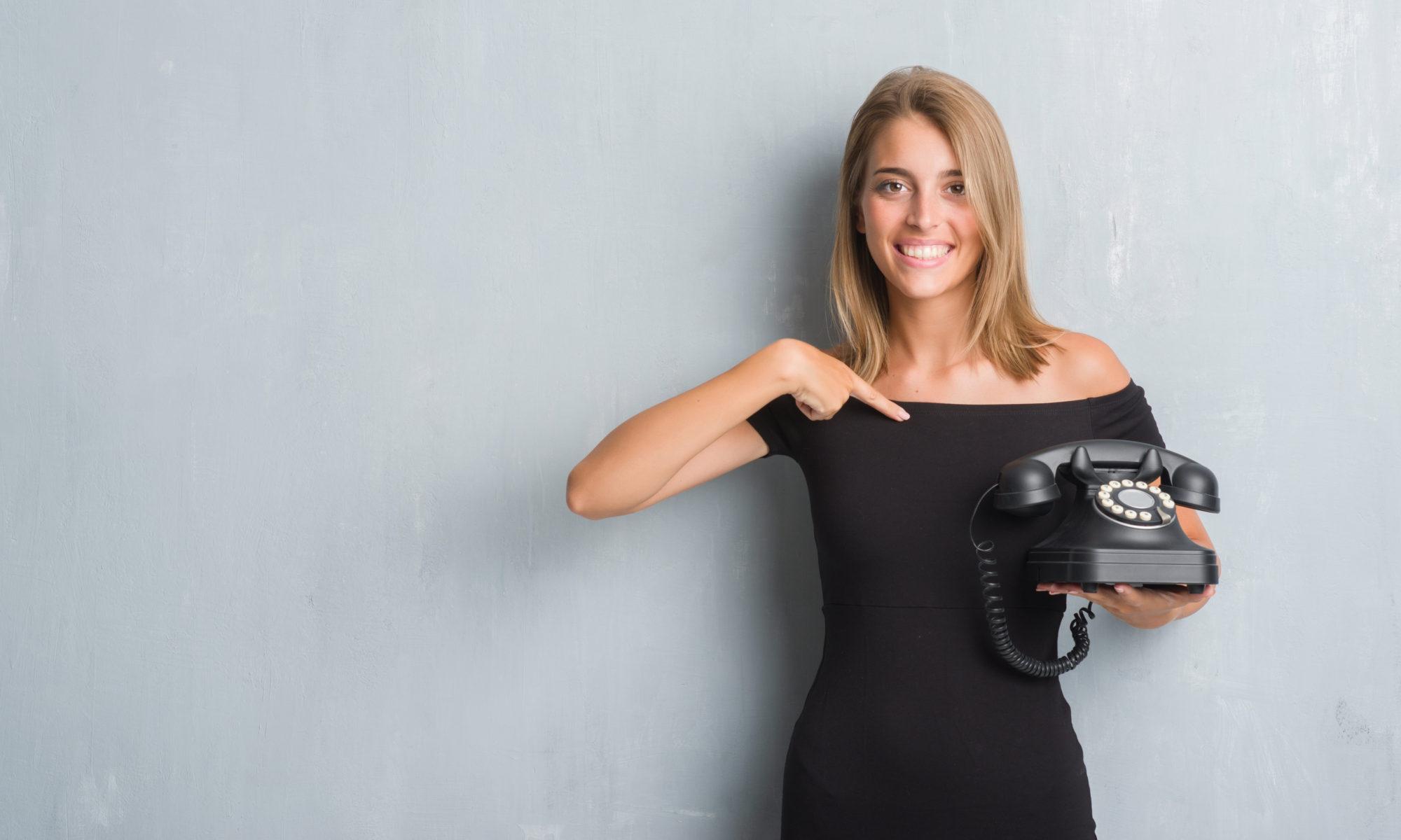 Dziewczyna w czarnej sukience z telefonem stacjonarnym w stylu retro