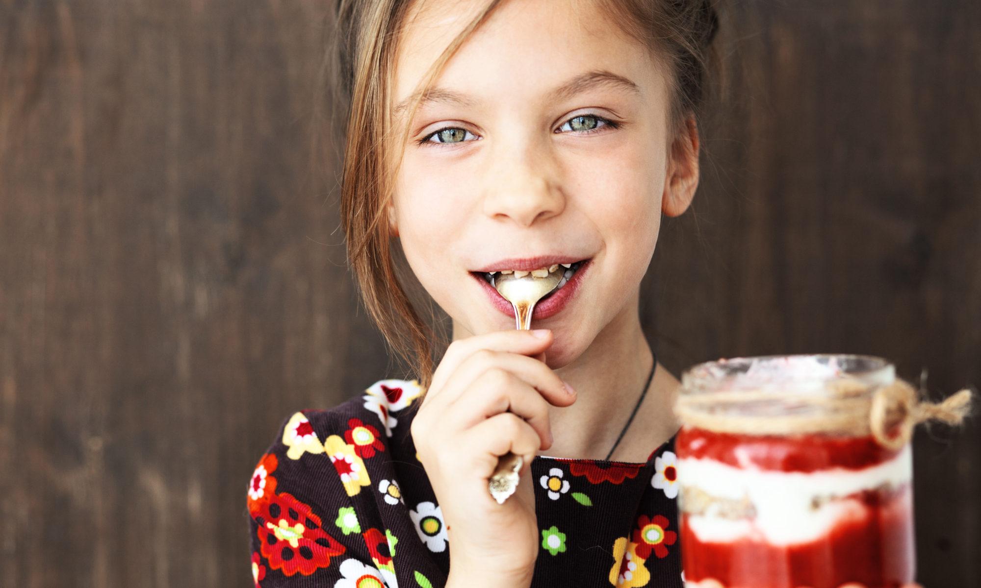 Dziewczynka jedząca zdrowy kolorowy deser