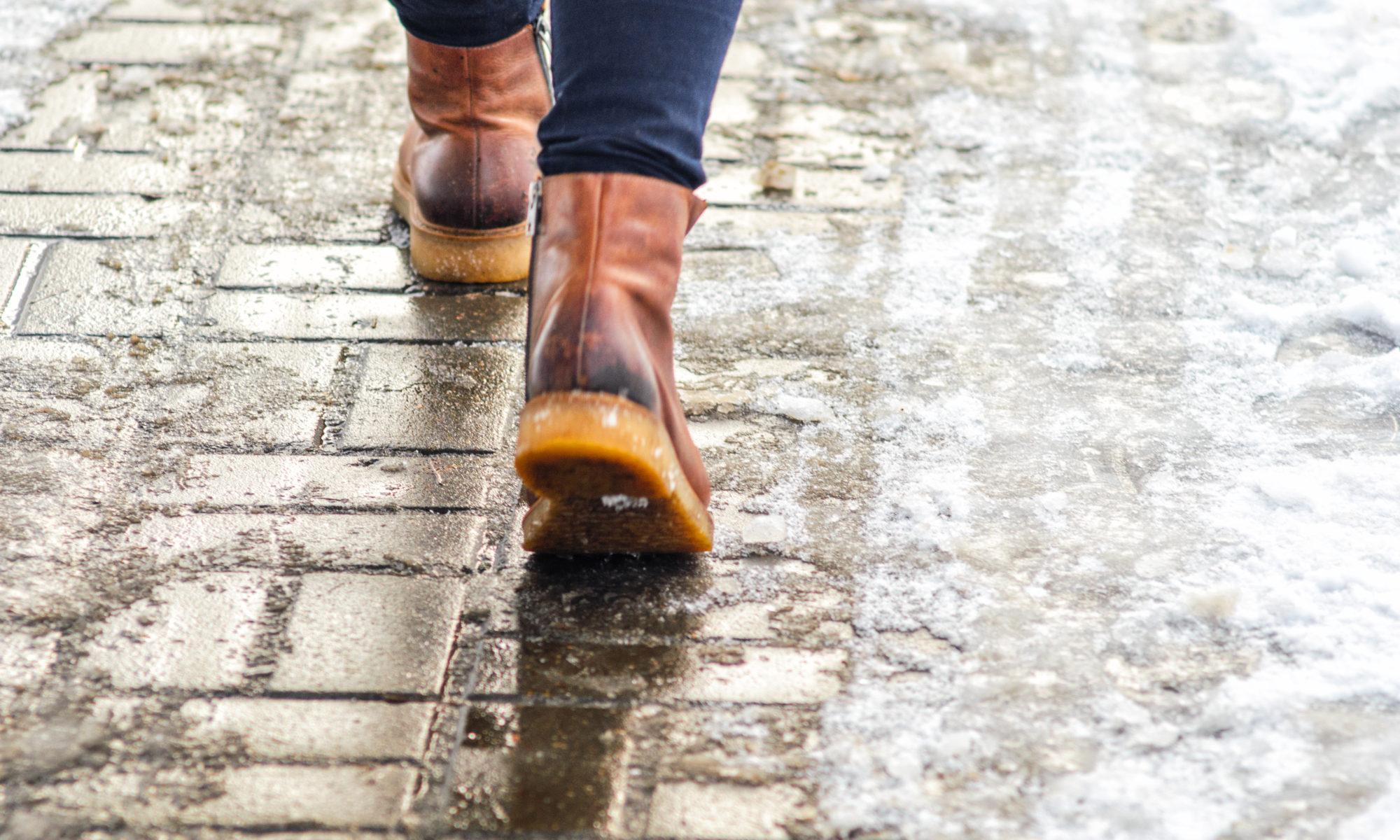 Mężczyzna spacerujący ośnieżonym chodnikiem