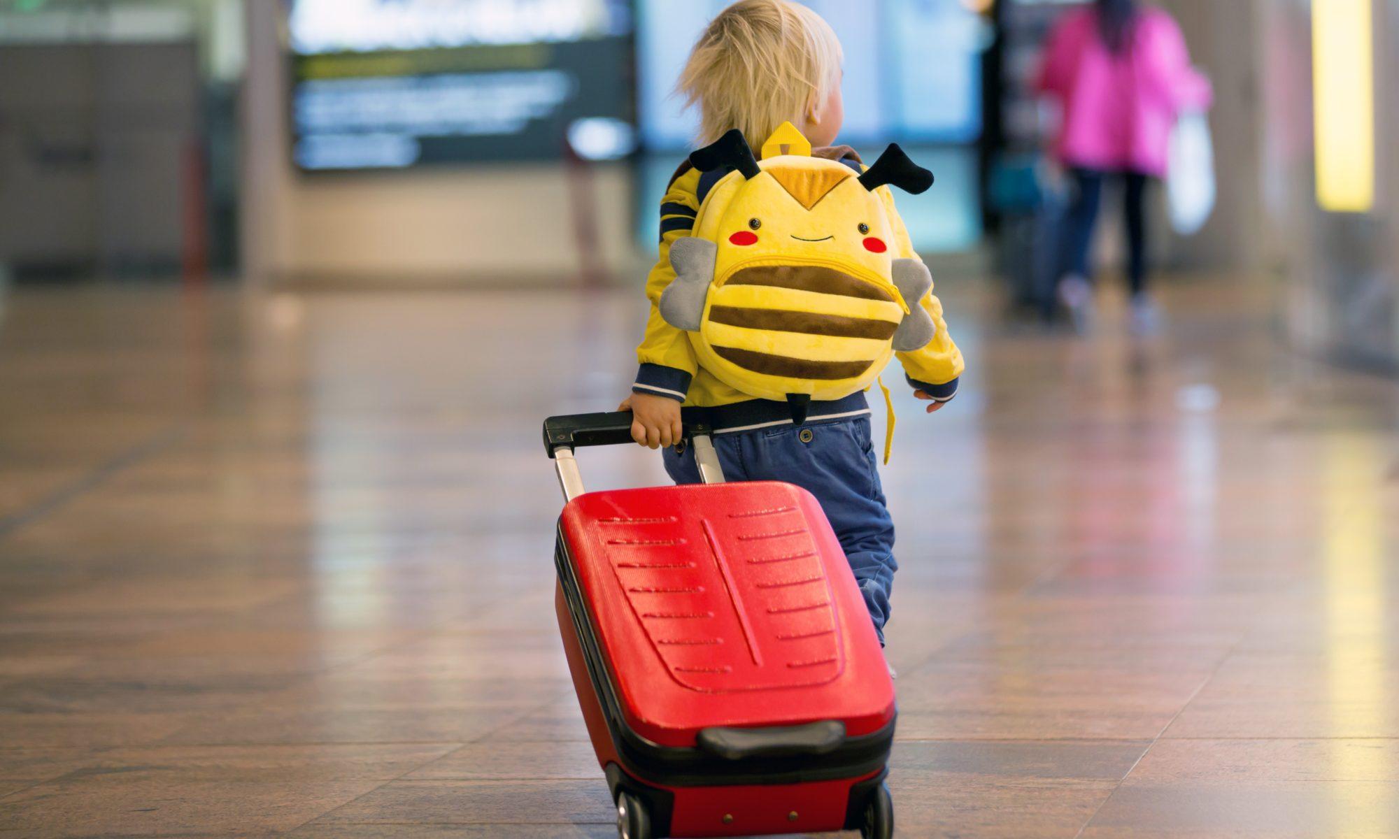 małe dziecko z walizką na lotnisku