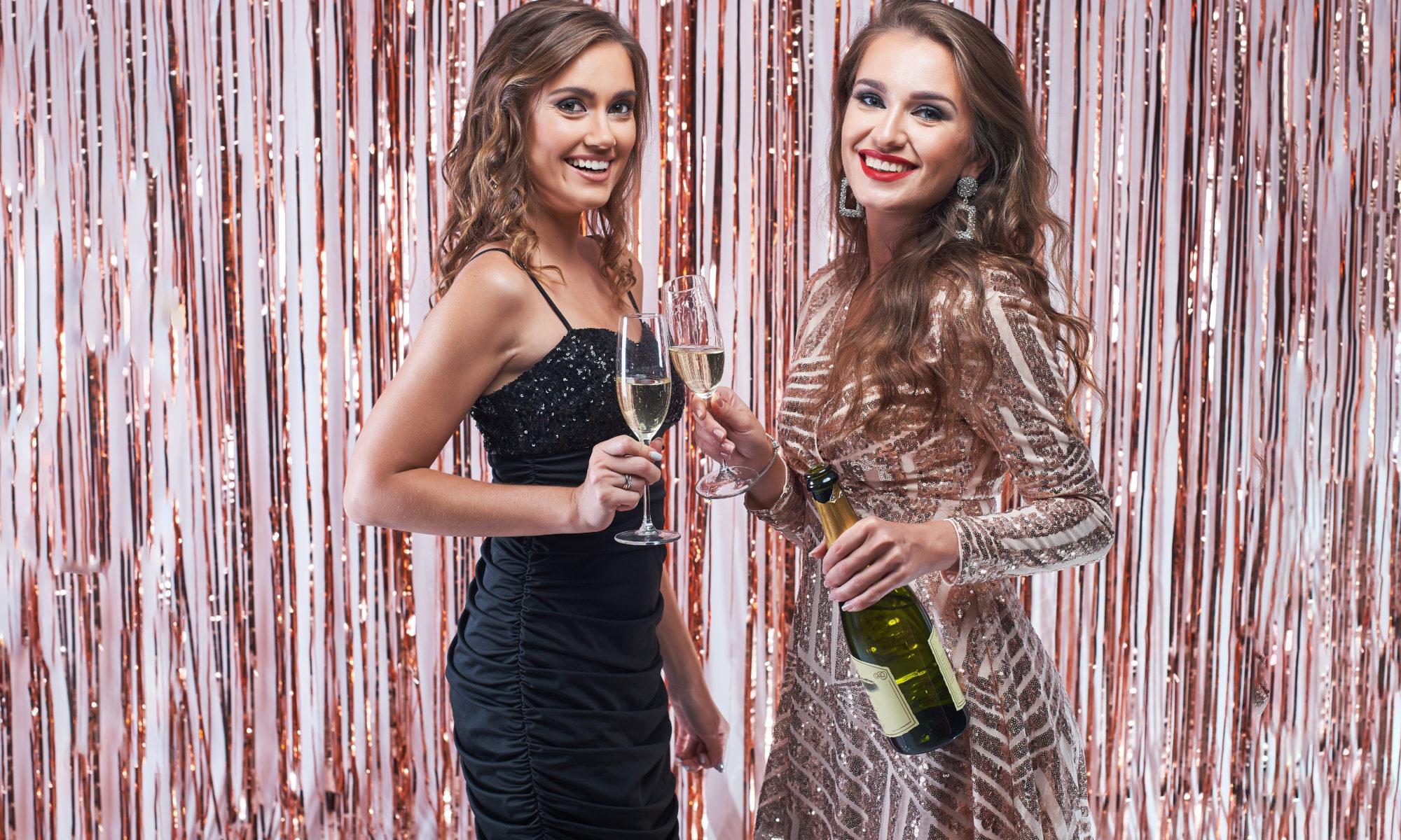 dwie imprezowe dziewczyny z butelką szampana