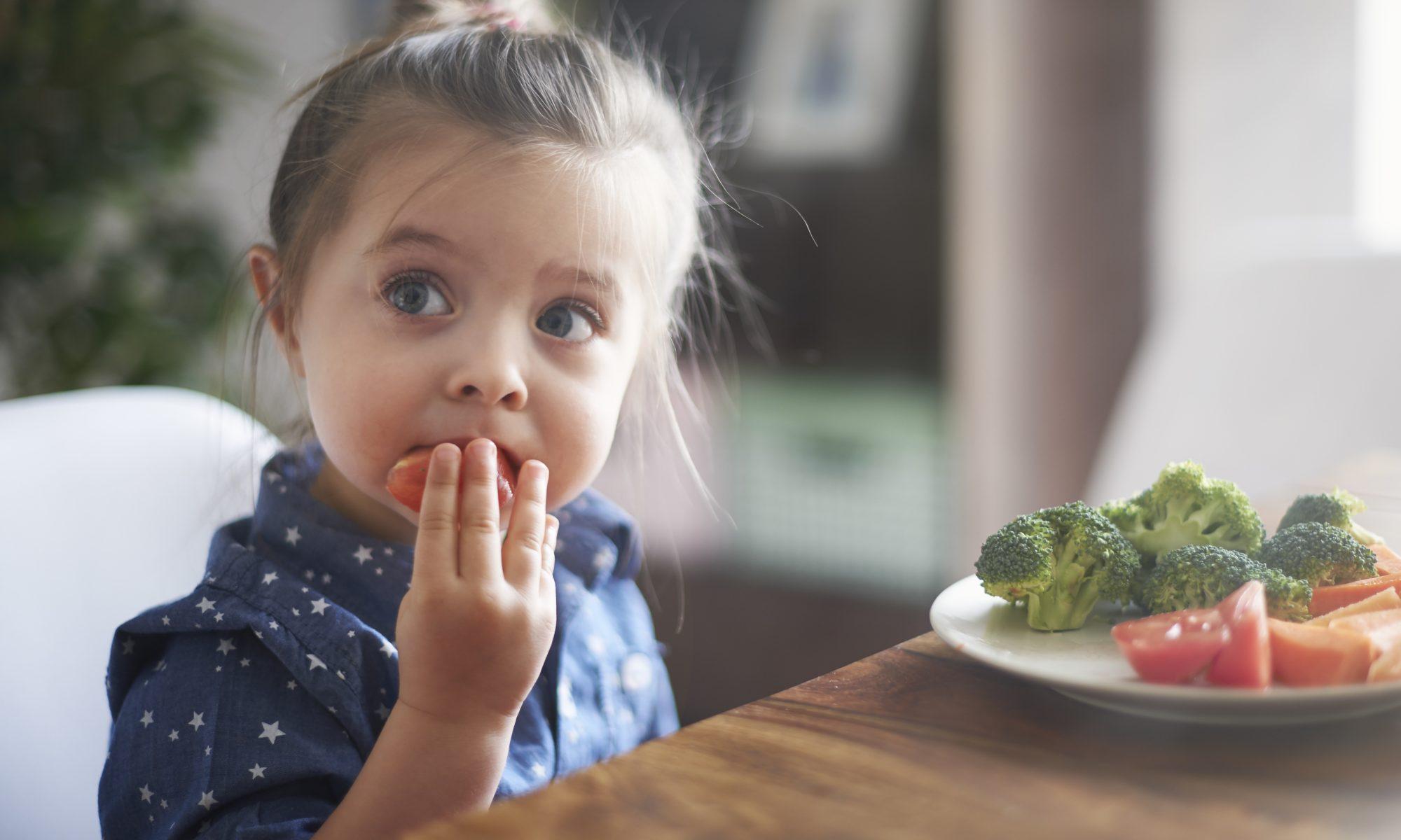 dziewczynka jedząca brokuły pomidory