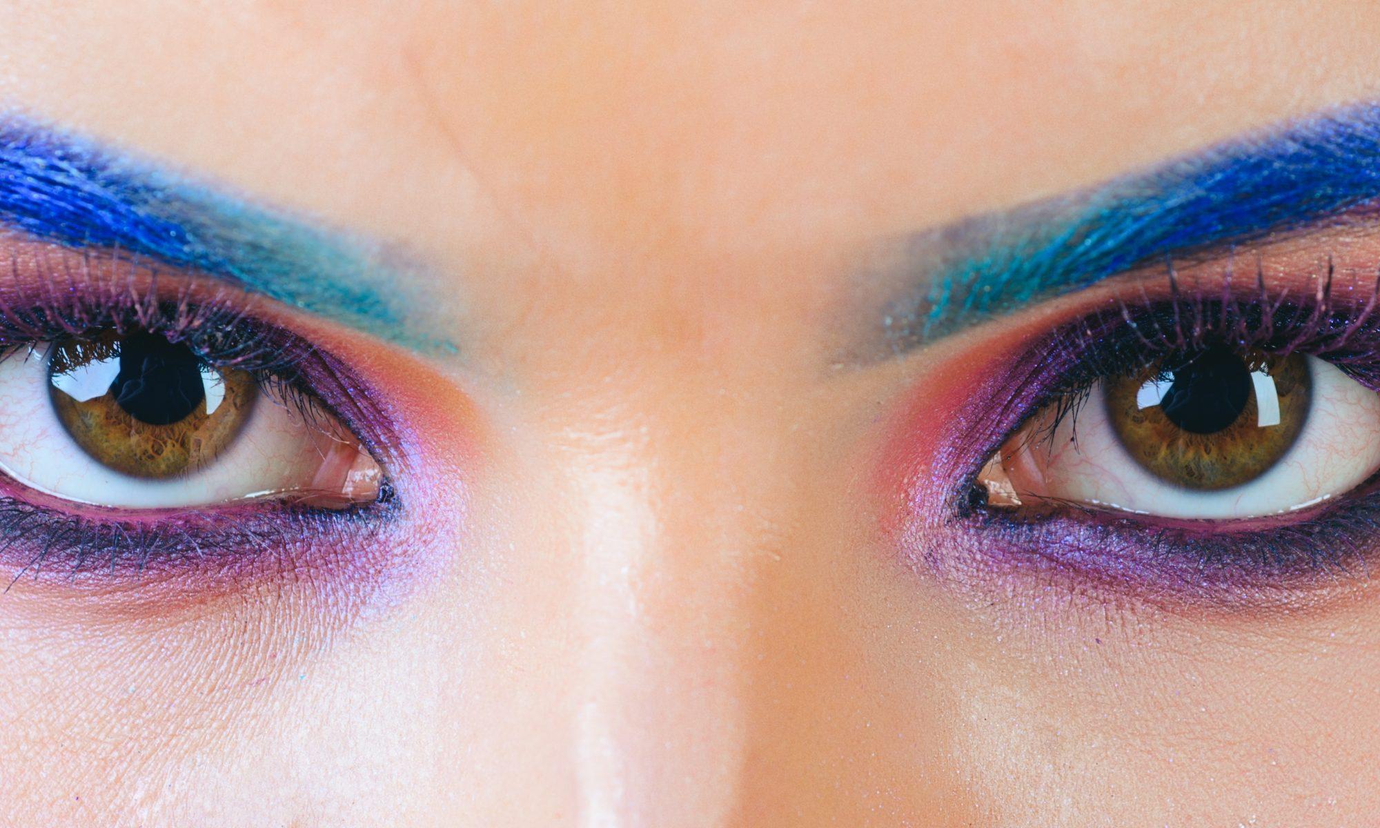 zbliżenie na kobiece oczy w neonowym makijażu