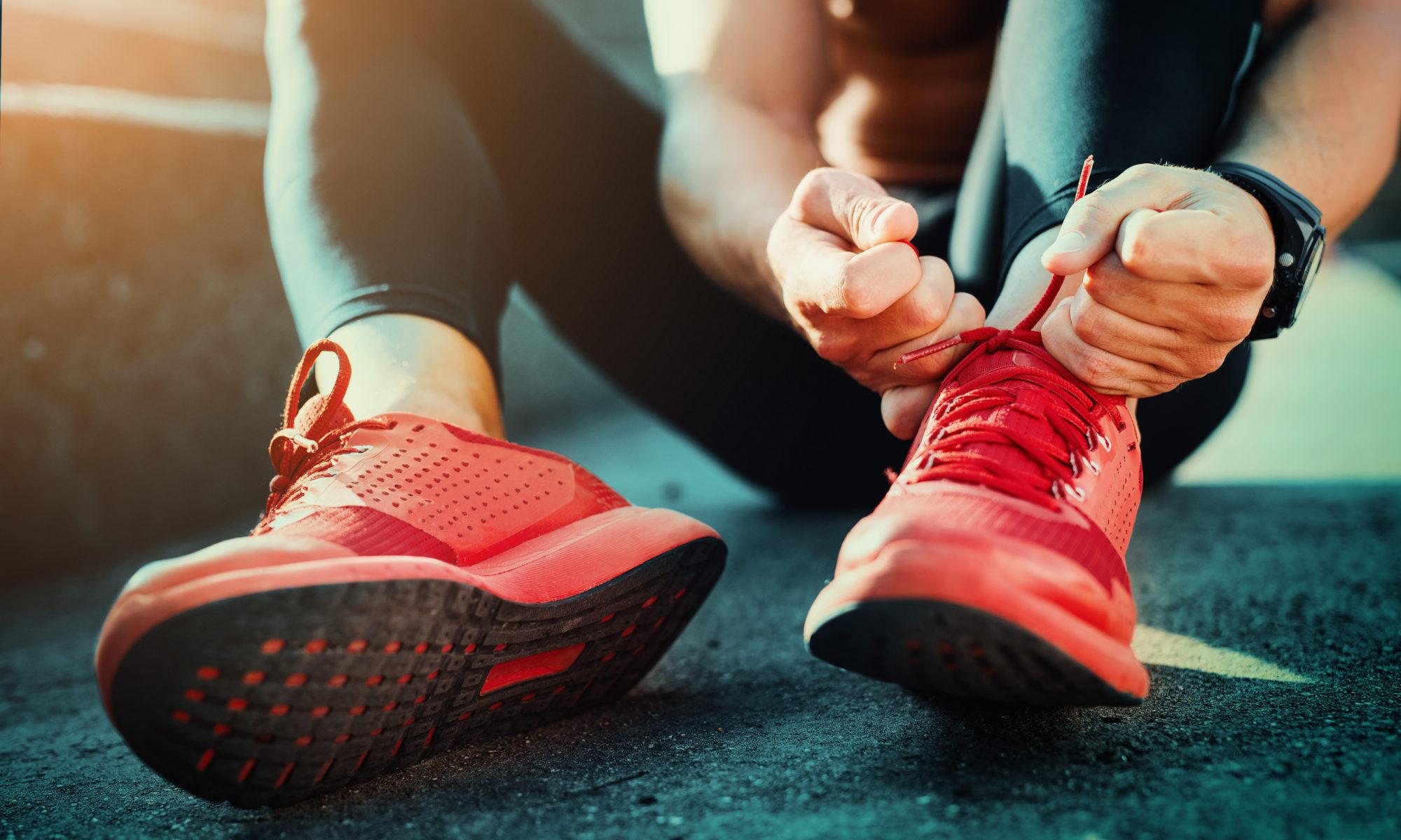 wiązanie pomarańczowych butów sportowych
