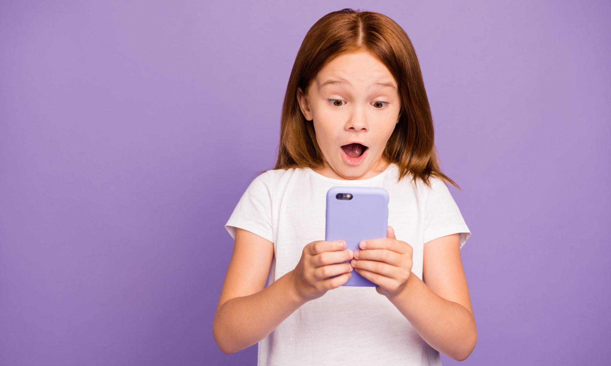 rudowłosa dziewczynka ze smartfonem
