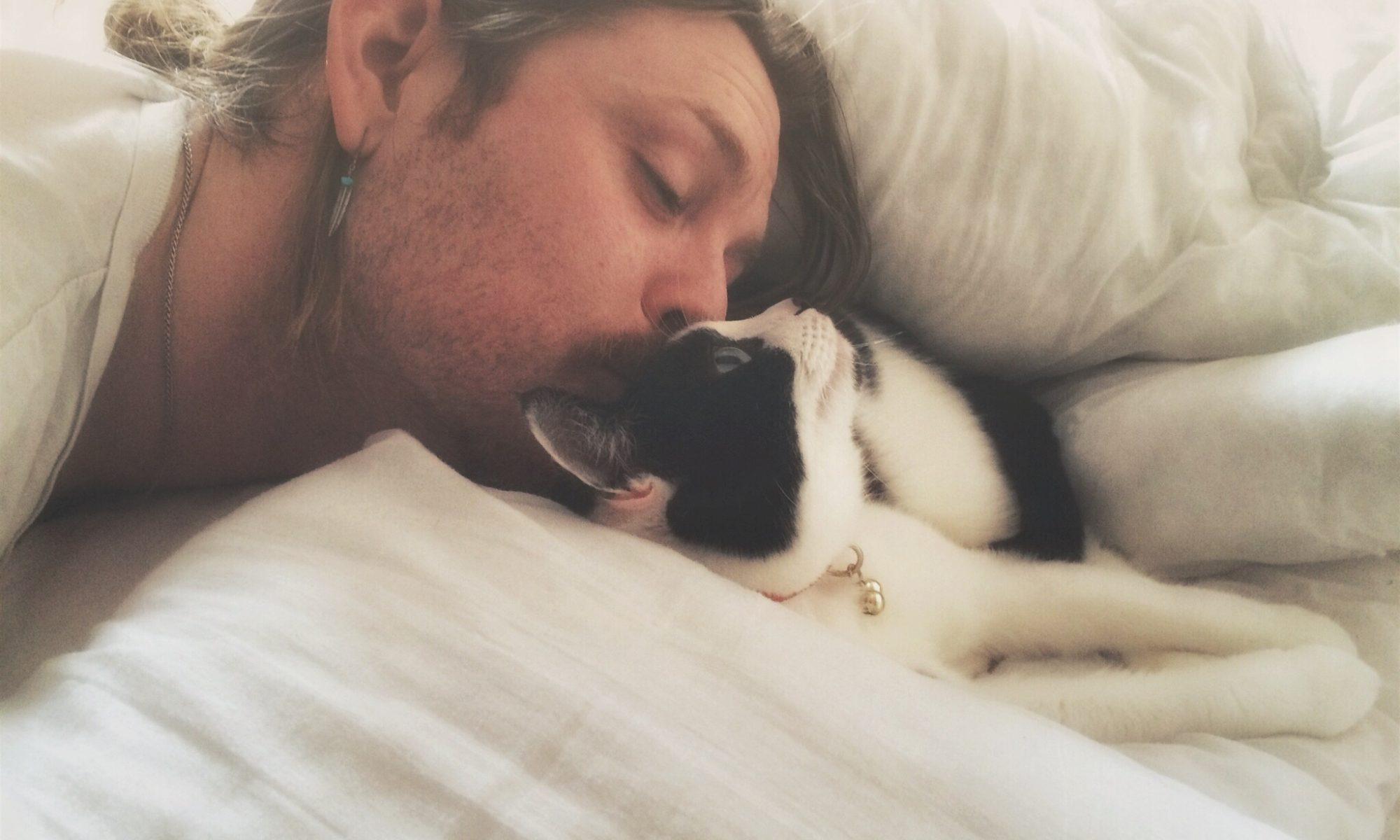 młody mężczyzna w łóżku całujący kota
