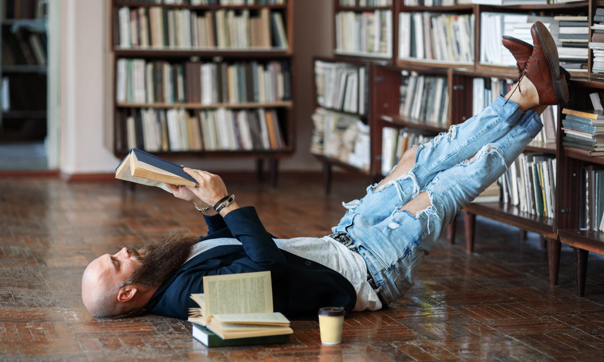 mężczyzna z brodą leżący na podłodze biblioteki